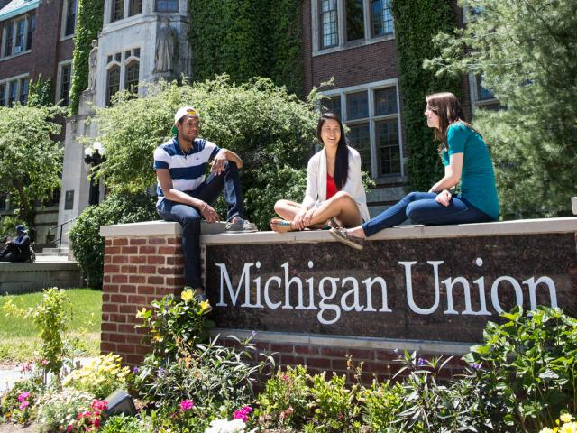 Students sitting on Michigan Union sign