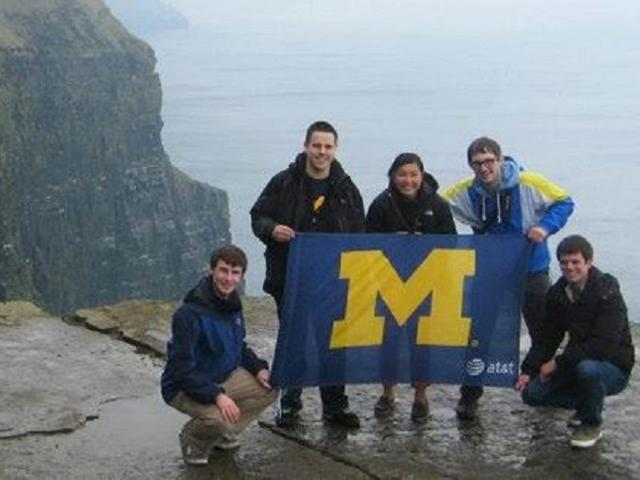 Students standing on cliff with Michigan flag